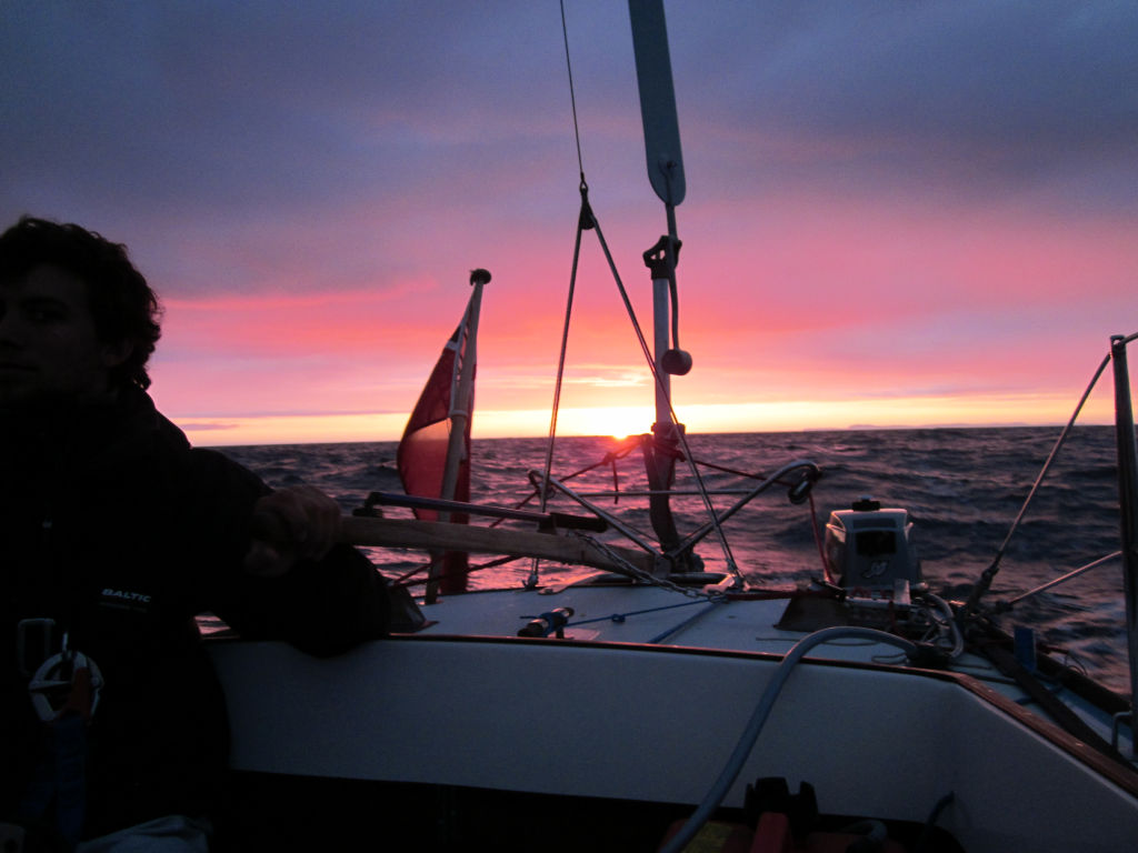 A sailboat under way at sunset using a Neptune self steering windvane
