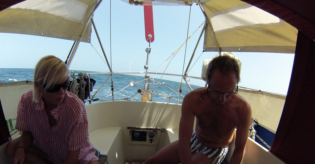 Couple relaxin in the yacht cockpit while being steered by a Neptune self steering windvane
