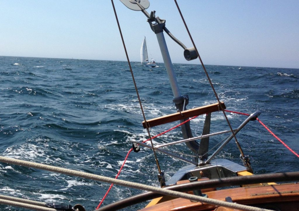 A sailboat at sea with a Neptune self steering windvane