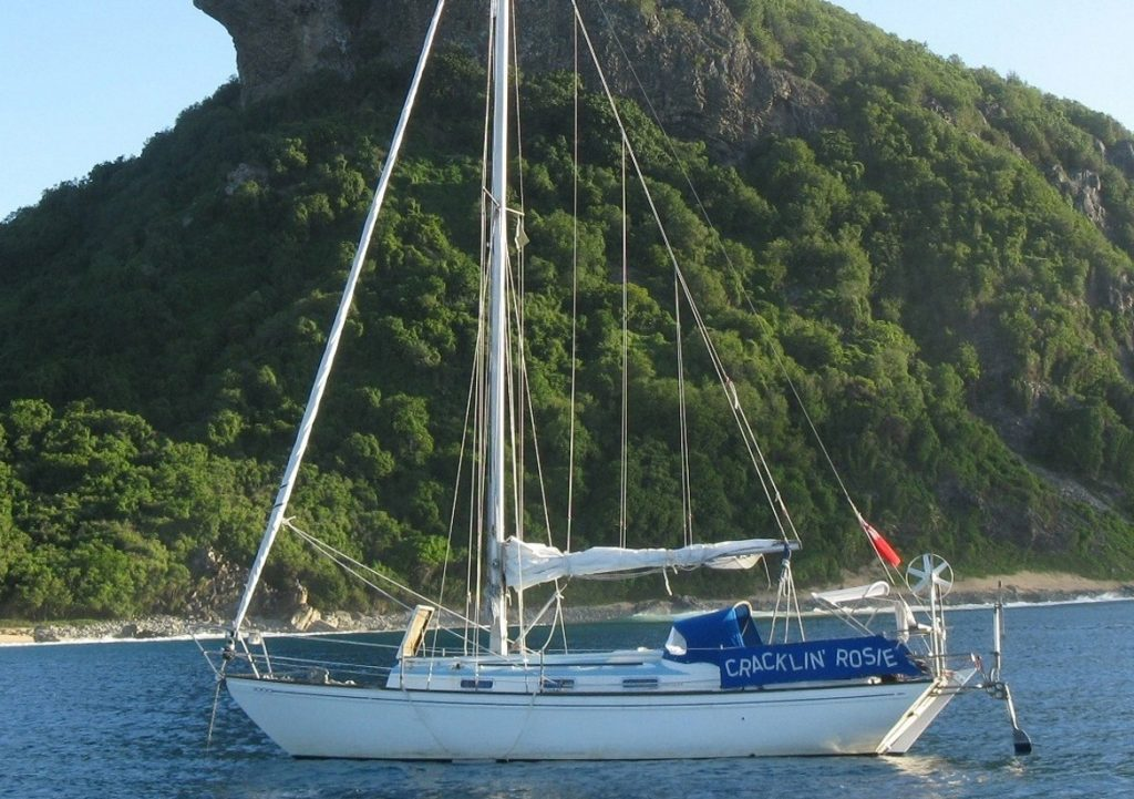A yacht anchored in a beautiful bay with a Neptune self steering windvane